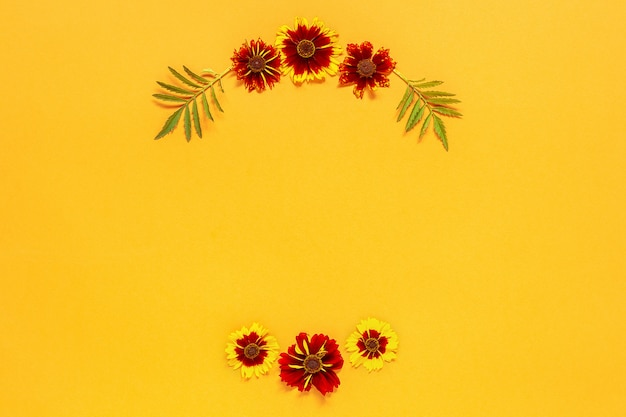 Flower composition. frame floral round wreath of yellow red flowers on orange background