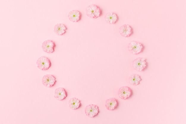花の組成。パステルピンクの背景にピンクの桜の花で作られたフレーム。フラットレイ。上面図。結婚式、バレンタインデー、女性の日のコンセプト