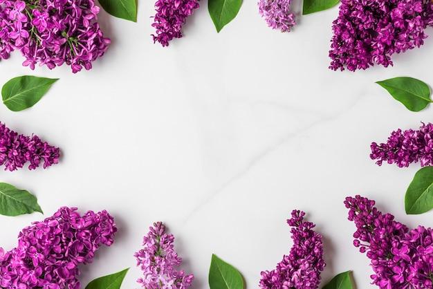 花の組成。白い表面に春紫のライラックの花で作られたフレーム