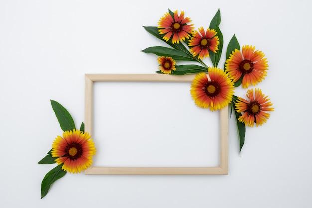꽃 조성. 흰색 배경에 노란색 오렌지 꽃의 프레임