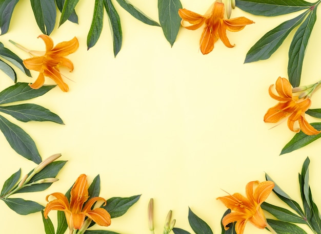 Flower composition. frame of yellow-orange lily flowers and green leaves on a yellow background, space for text. spring background. flat lay.