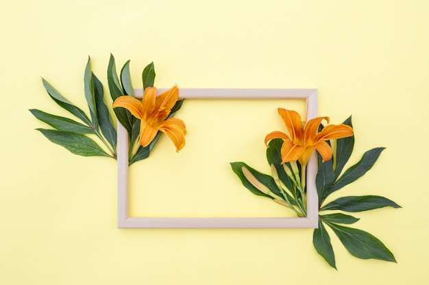 Flower composition. frame of yellow-orange lily flowers and green leaves on a yellow background