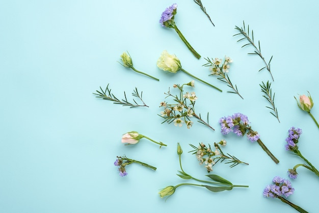 Flower composition of roses, eustoma and lemongrass on blue