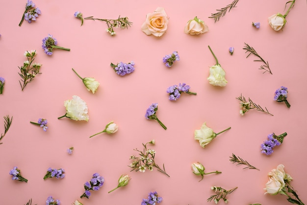 Flower composition, roses, eustoma, limonium on pastel pink background, flat lay, top view, spring concept