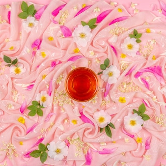 Flower composition of white and pink flowers and and a cup of tea on pink cloth