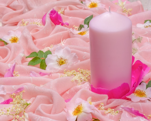 Flower composition of white and pink flowers and a pink candle on pink cloth