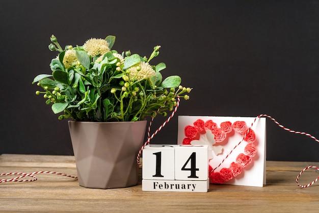 木製のカレンダーとピンクの背景にバレンタインデーの心と花の構成