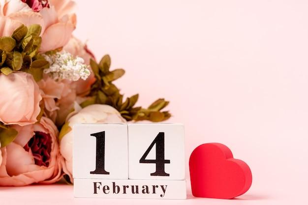 木製のカレンダーとピンクの背景にハートと花の構成
