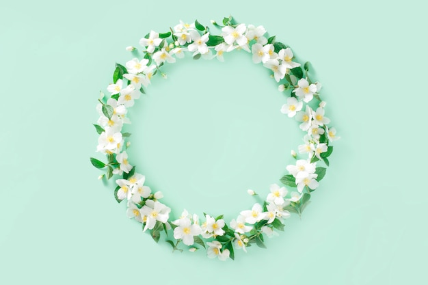 Цветочная композиция. венок из белых весенних цветов жасмина на пастельно-зеленом