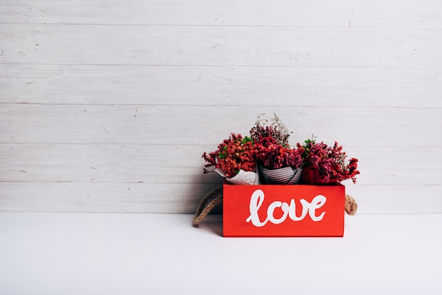 Flower cones in the love box on white desk against wooden backdrop