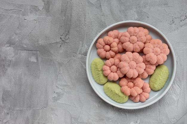 灰色の背景上の皿に花のクッキー。春休み料理のコンセプトです。