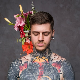 Flower decoration behind the tattooed and pierced young man against grey backdrop