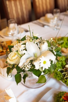Flower decorations on the banquet table, prepared for event party or wedding