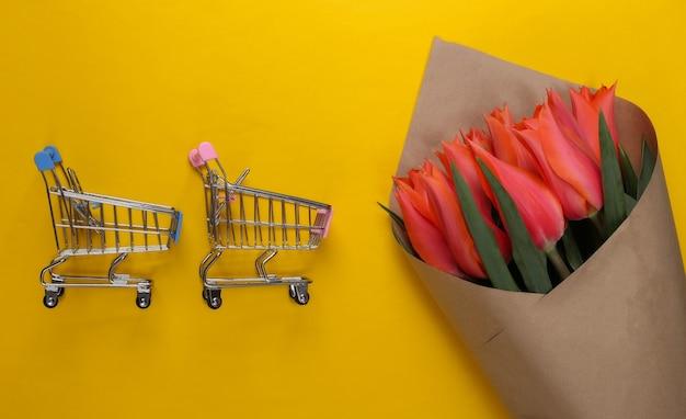 Доставка цветов. букет тюльпанов с тележкой супермаркета на желтом