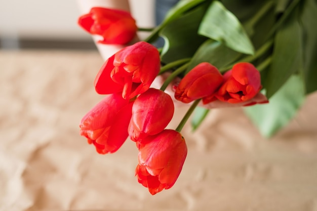 Доставка цветов. флорист, составляющий букет красных тюльпанов. руки женщины завязывают бант шпагатом.