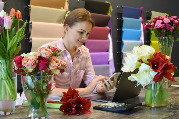 Flower delivery service. florist seller with a telephone. interior flowers