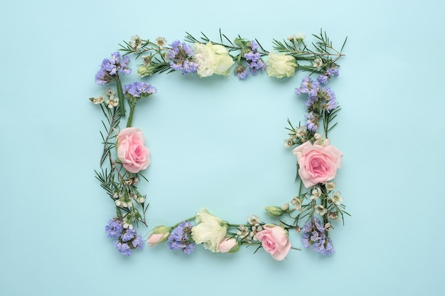 Flower frame on blue background with copy space, composition of roses, limonium, eustoma, top view, flat lay