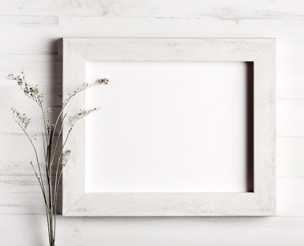Flower and a frame on wooden wall