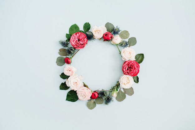 Flower frame wreath made of beige and red roses, eucalyptus branches on pale pastel blue