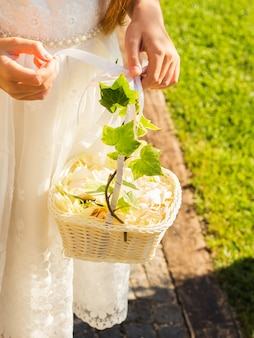 Flower girl in white dress with basket of petals