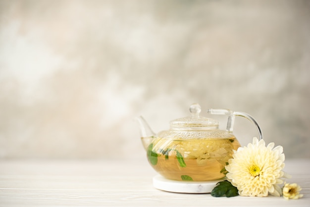 Flower herbal tea with chrysanthemum petals in a glass teapot, close-up