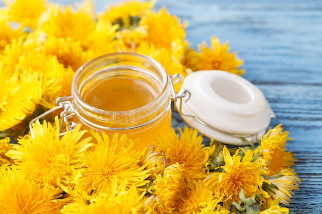 ガラスの瓶と木製のテーブルにタンポポの花蜂蜜