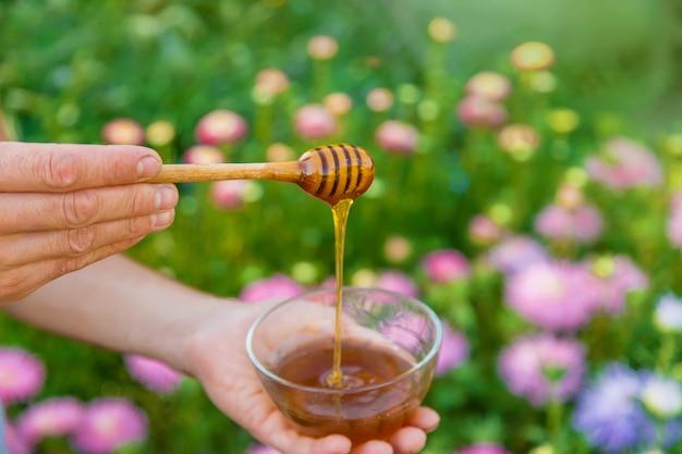 Цветочный мед в руках мужчины. выборочный фокус. природа.