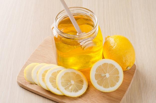 Flower honey and lemon on light background.