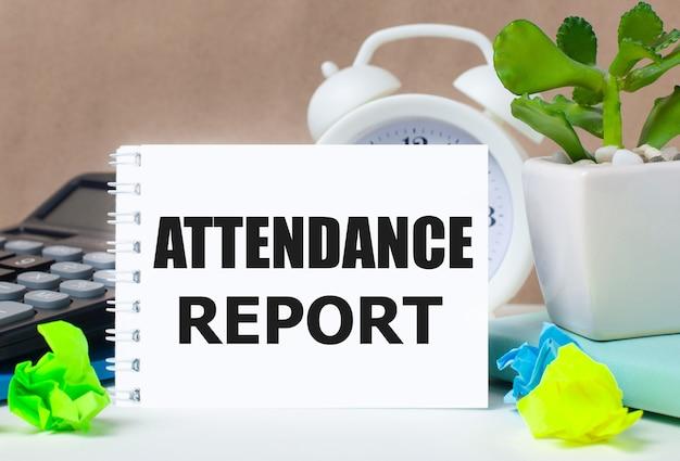 植木鉢、電卓、白い目覚まし時計、色とりどりの紙、デスクトップに「出席レポート」と書かれた白いノート。