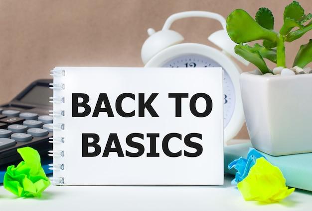 植木鉢、電卓、白い目覚まし時計、色とりどりの紙、デスクトップに「基本に戻る」というテキストが書かれた白いノートに花を咲かせます。