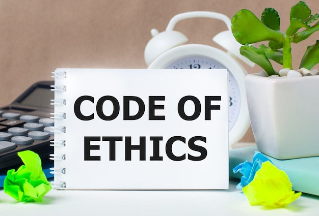 Цветок в горшке, калькулятор, белый будильник, разноцветные бумажки и белый блокнот с текстом кодекс этики на рабочем столе.