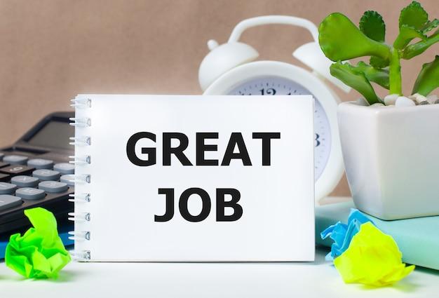 Цветок в горшке, калькулятор, белый будильник, разноцветные бумажки и белый блокнот с надписью great job на рабочем столе.