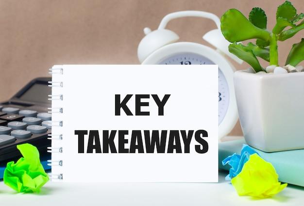 植木鉢、電卓、白い目覚まし時計、色とりどりの紙、デスクトップに「重要なポイント」というテキストが書かれた白いノート。