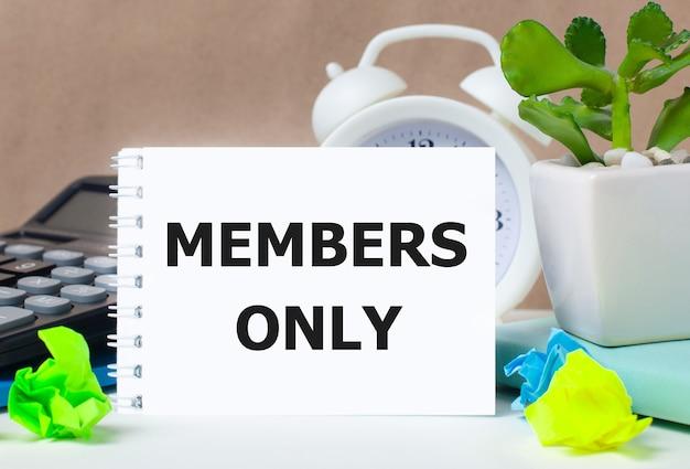 植木鉢、電卓、白い目覚まし時計、色とりどりの紙、デスクトップに「メンバーのみ」と書かれた白いノート。