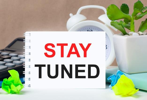 鍋に花を咲かせ、電卓、白い目覚まし時計、色とりどりの紙、白いノートに「staytuned」というテキストをデスクトップに表示します。