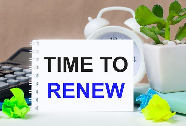 Цветок в горшке, калькулятор, белый будильник, разноцветные бумажки и белый блокнот с текстом «время обновить» на рабочем столе.