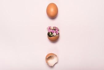 ピンクのテーブルに壊れた卵を花します。