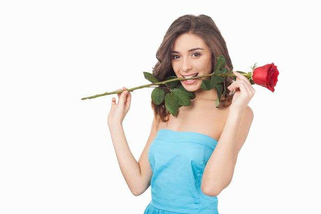 그녀의 입에 꽃입니다. 빨간 장미를 입에 물고 흰색으로 격리된 채 웃고 있는 매력적인 젊은 여성