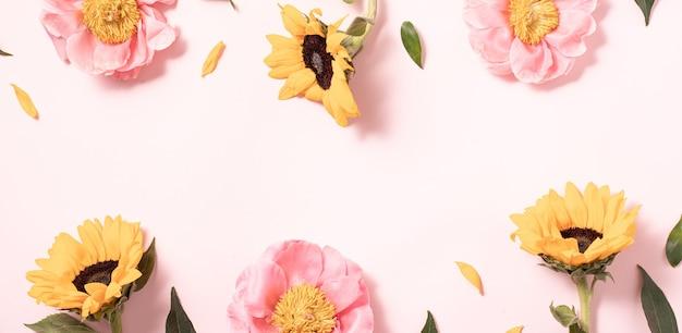 파스텔 핑크 배경에 플랫 스타일의 꽃 레이아웃. 최소한의 자연 플랫레이. 크리에이 티브 여름 플랫 누워 및 상위 뷰 배경.