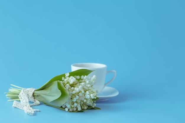 青色の背景にスズランの花