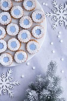 明るい冬の上に設定された白いマーマーボード上の青いアイシングで花リンツァークッキー
