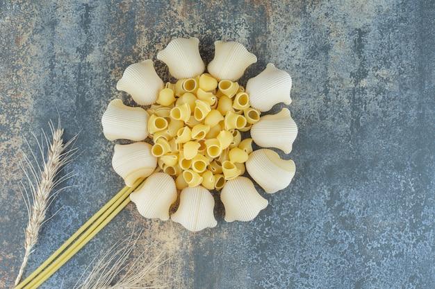 大理石の背景に、パスタと小麦のスパイクで作られた花。