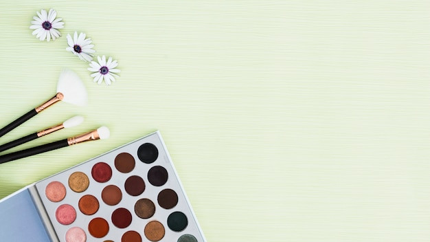 Flower; makeup brushes and eyeshadow palette on mint textured backdrop
