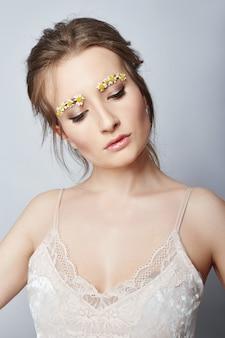 얼굴 소녀의 꽃잎, 얼굴 피부에 수분을 공급하고 주름을 줄이고 건강한 피부를 청소하는 여성 화장품. 여자의 얼굴과 몸에 꽃을 피우는 주름개선 크림. 아름다운 머리카락과 입술