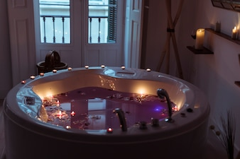 Flower petals on water in spa tub with burning candles on edges