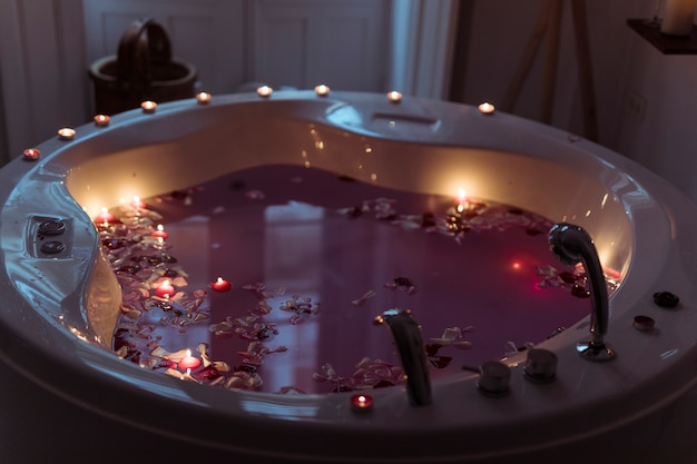 Flower petals in spa tub with water and burning candles on edges