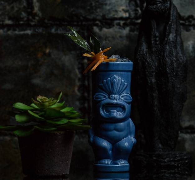 Flower plant inside a ethnic decorated vase and a suculentus around