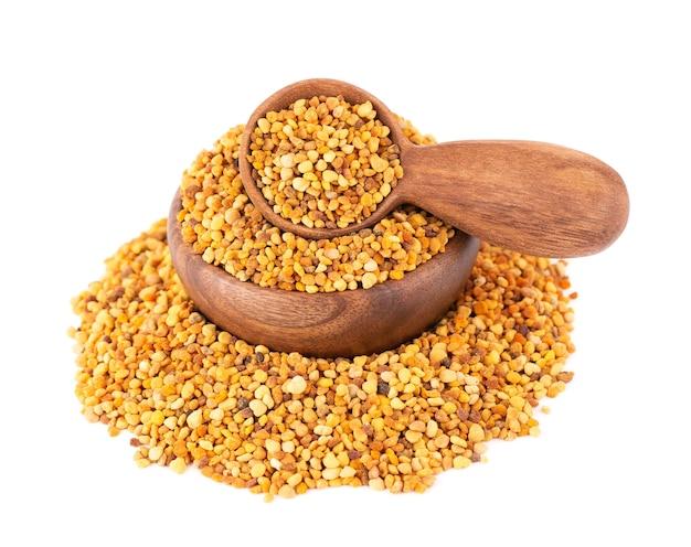 Цветочные зерна пыльцы в деревянной миске и ложке, изолированные на белом.