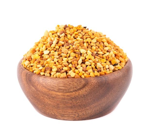 Цветочные зерна пыльцы в деревянной миске, изолированные куча пчелиной пыльцы или перги.