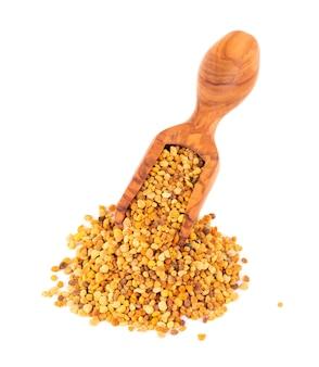 Flower pollen grains in wooden scoop, isolated   pile of bee pollen or perga.
